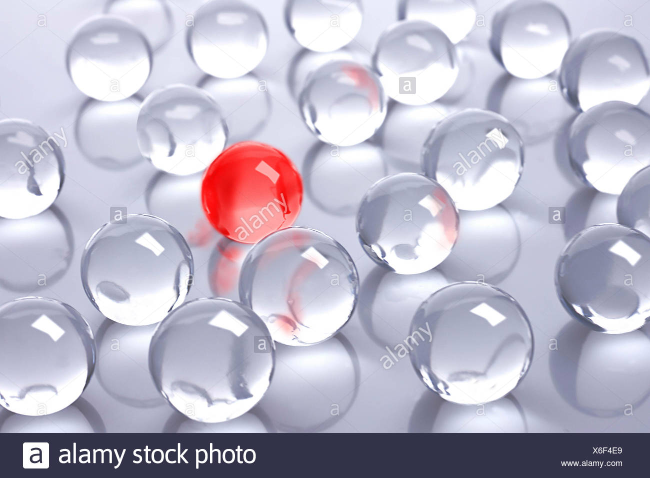 A red glass ball amidst many colourless glass balls - Stock Image