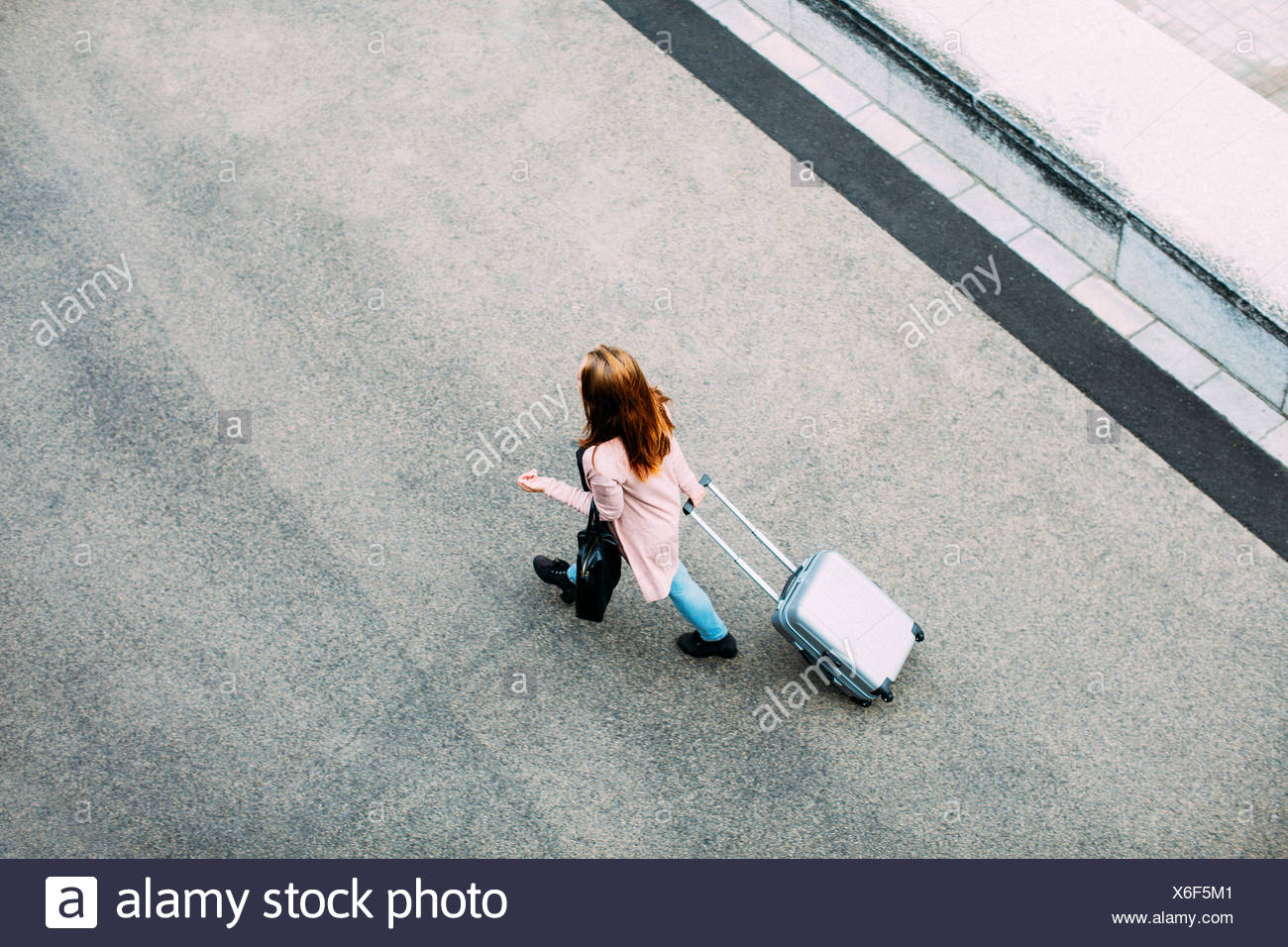 Top view of walking woman with wheeled luggage - Stock Image