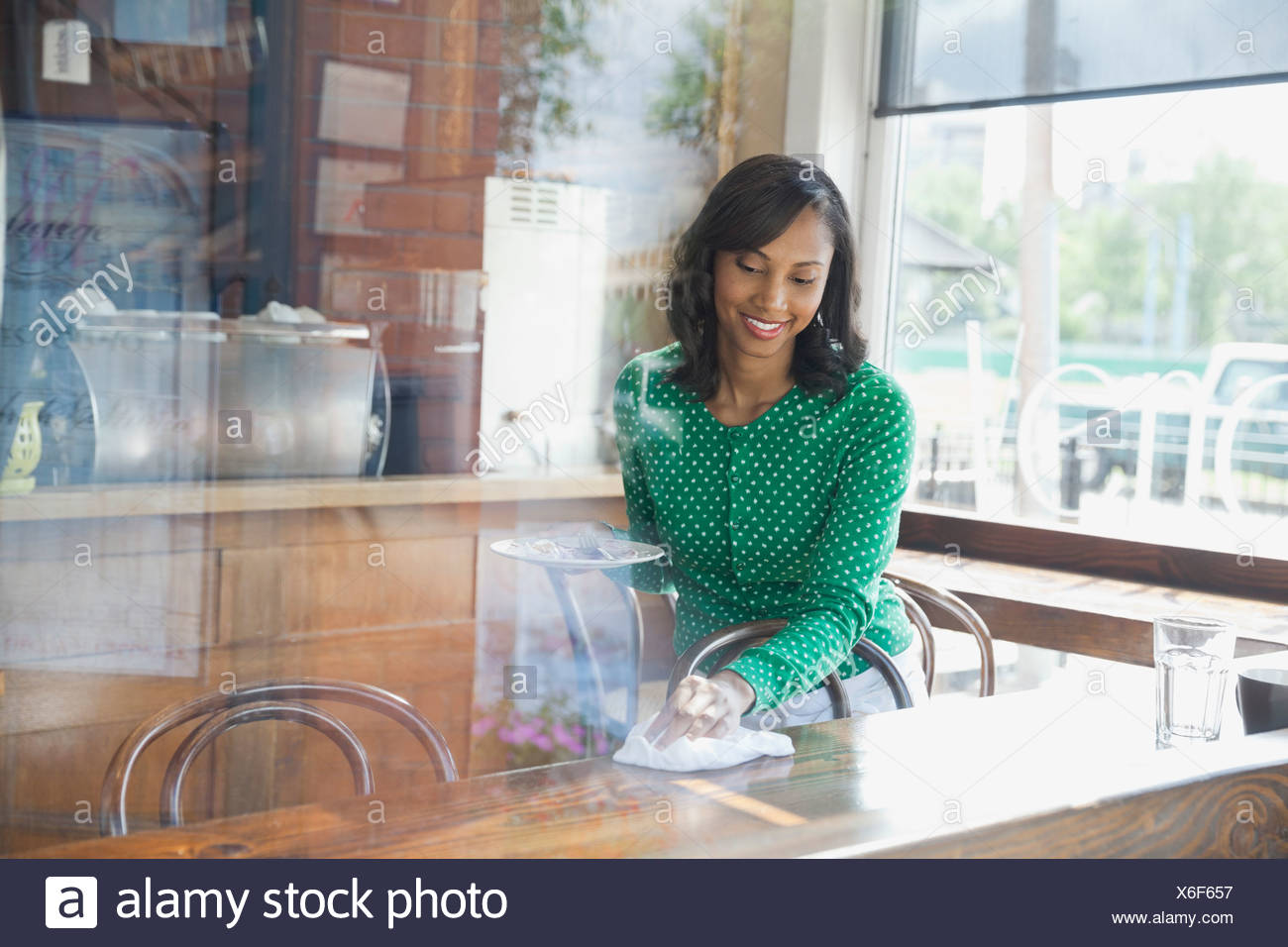 Smiling waitress cleaning table in cafe - Stock Image