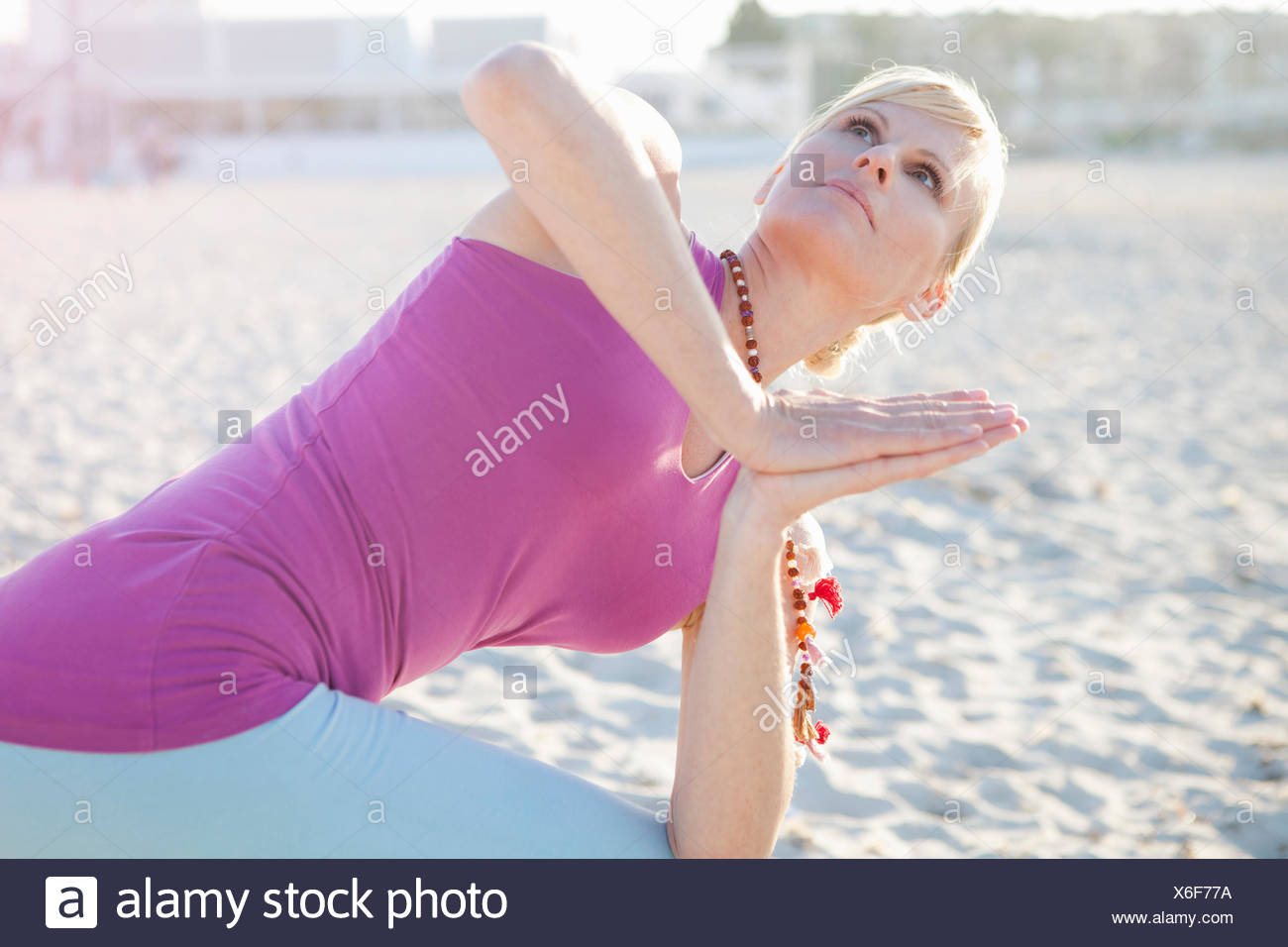 Woman in yoga prayer pose on the beach - Stock Image