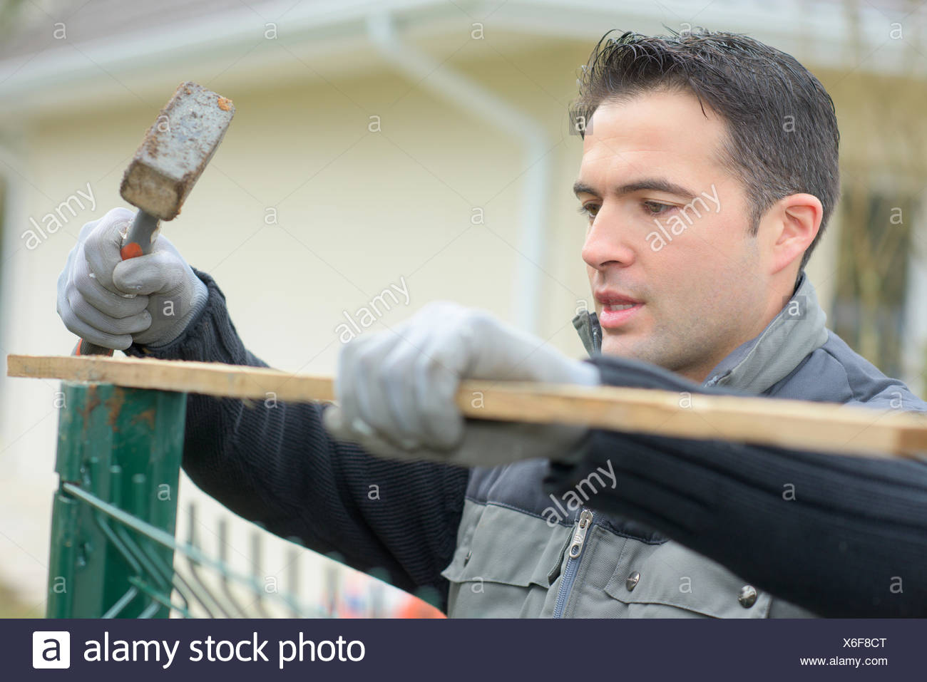 Hammering a fence into place - Stock Image