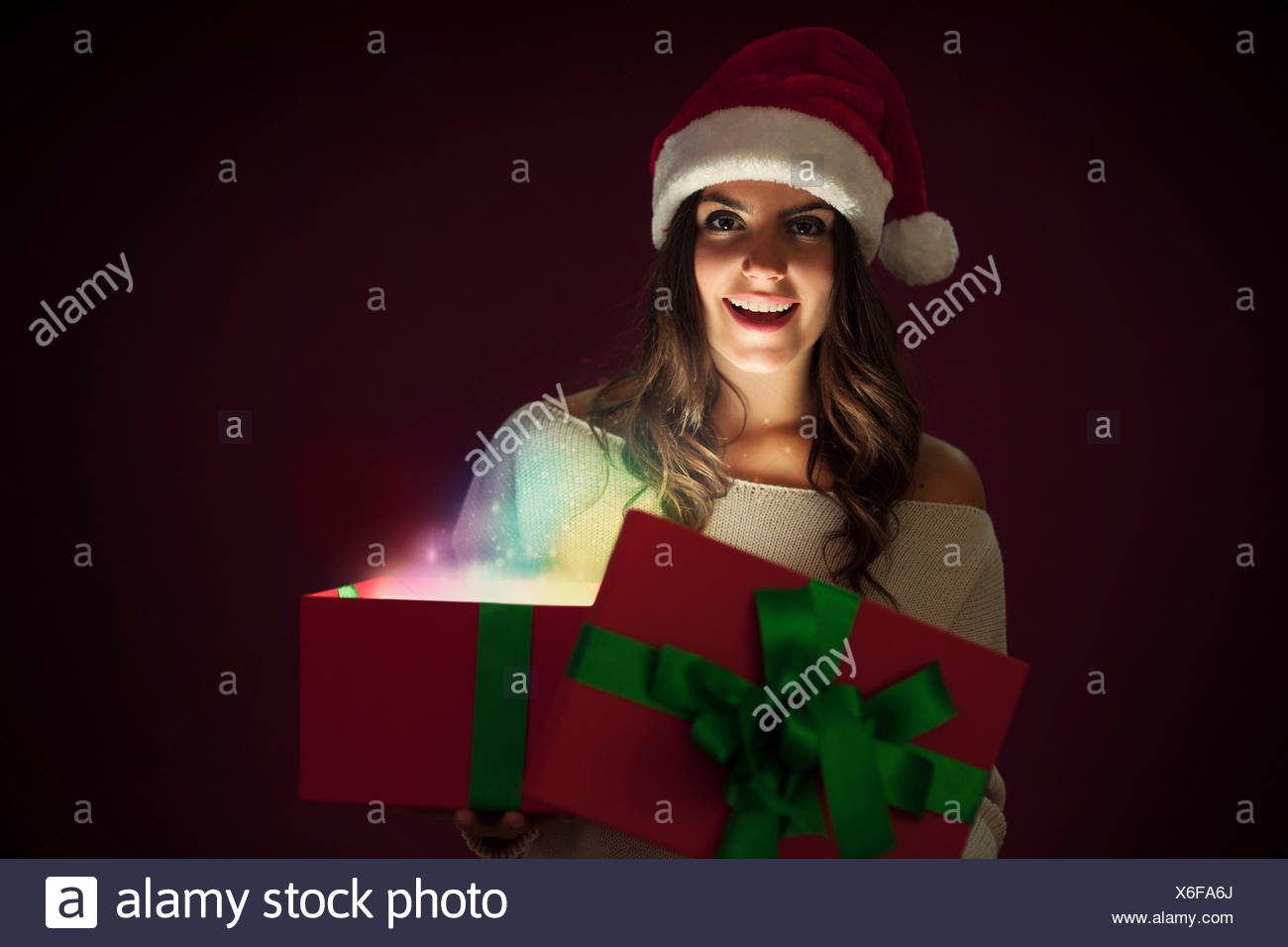 Woman with Santa hat opening magic gift Debica, Poland - Stock Image