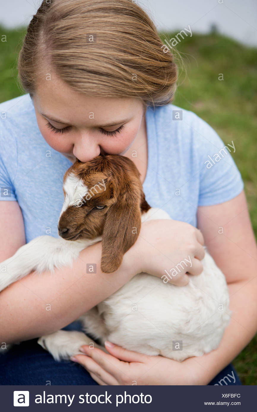 A girl cuddling a baby goat. - Stock Image