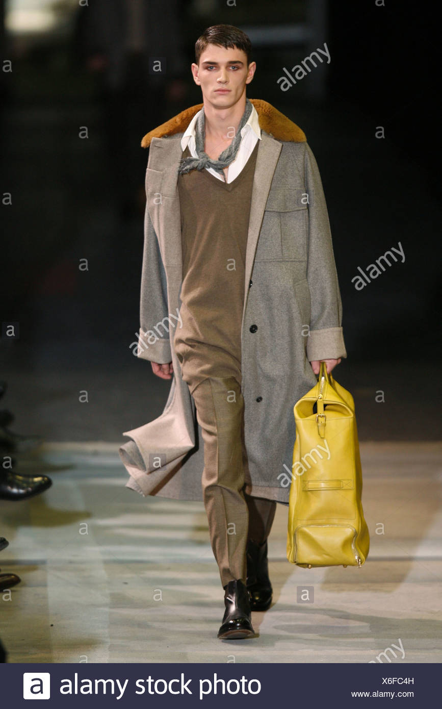 a6e2176b5f7 Yves Saint Laurent Paris Menswear Ready to Wear Autumn Winter Layers: Male  model carrying large yellow suitcase, wearing long