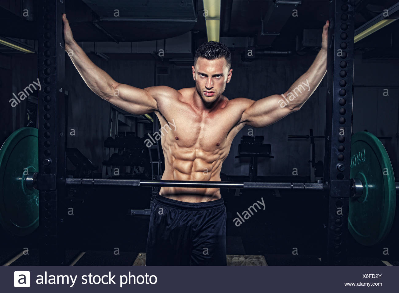 Physical athlete at Power Rack in gym - Stock Image