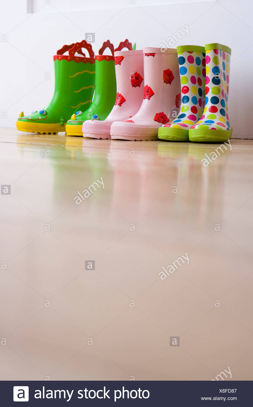 Three pairs of children's rubber boots, ground view - Stock Image