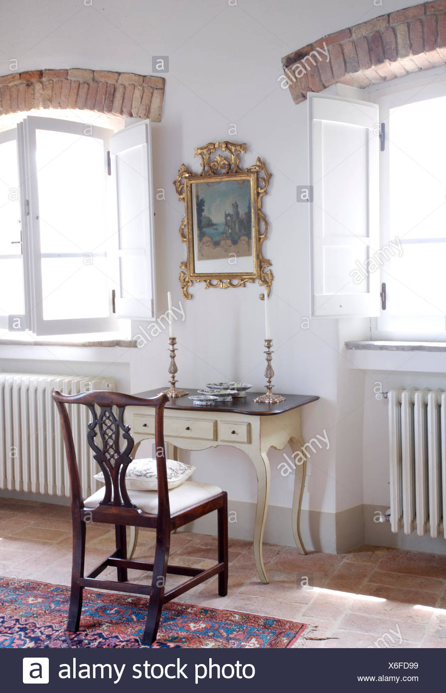 Gilt framed picture above small antique dressing table with silver candlesticks and antique chair in Italian bedroom Stock Photo