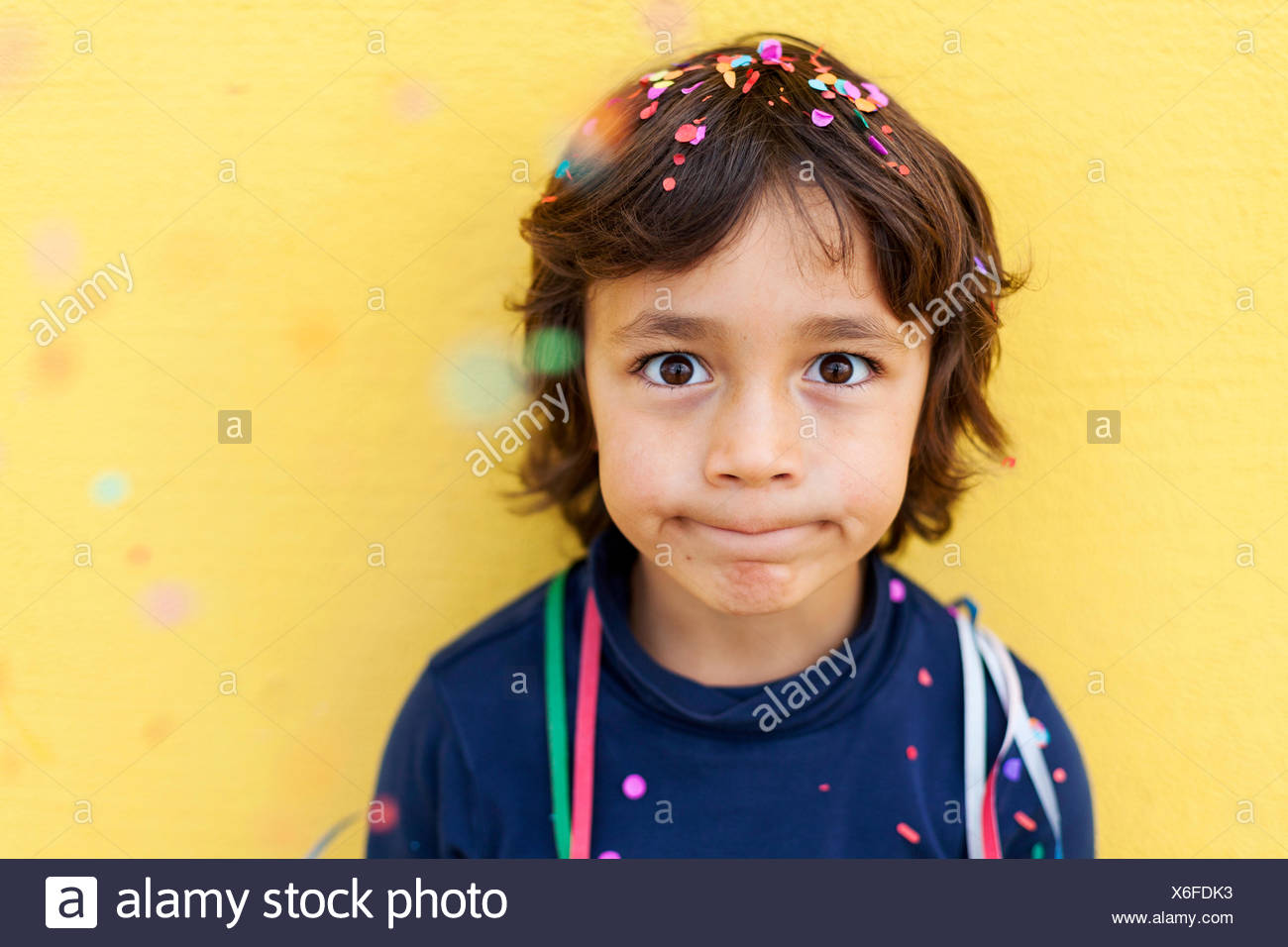 Little boy pulling funny face in front of yellow wall while confetti falling down on him - Stock Image