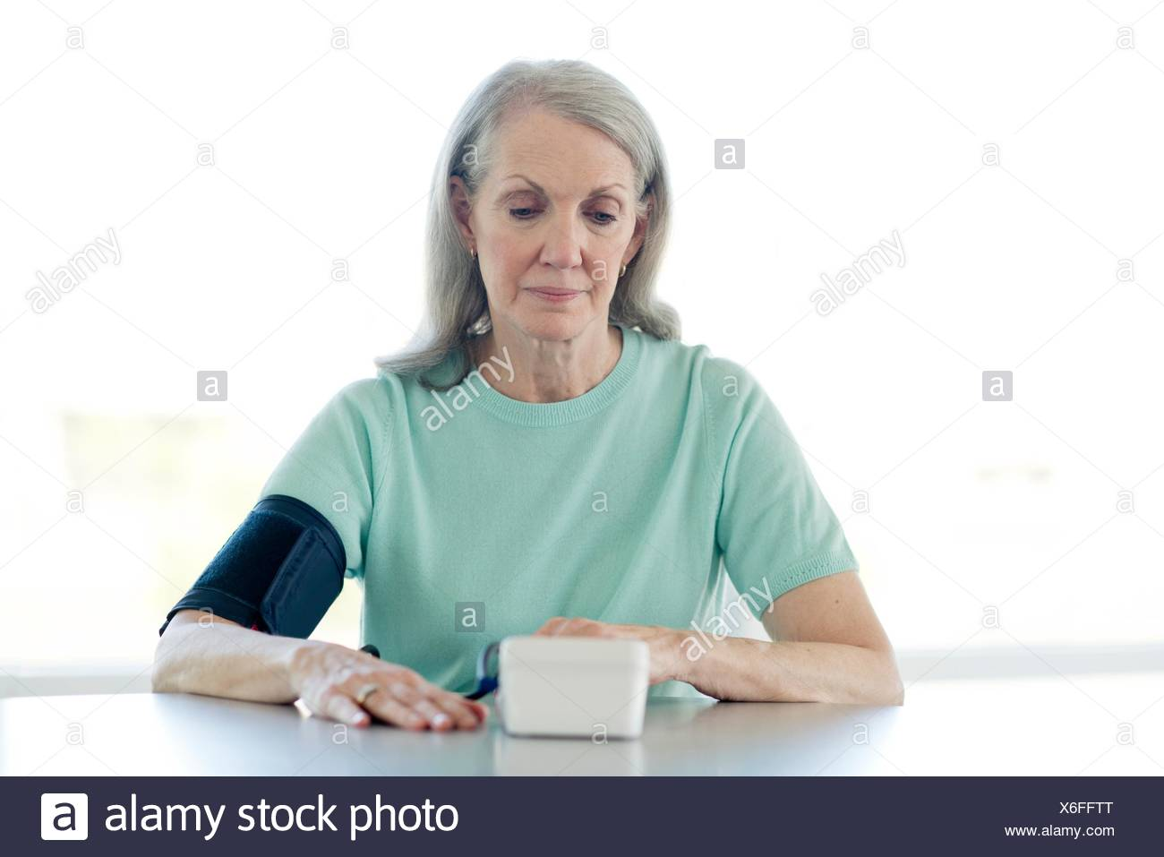Senior woman taking her own blood pressure. - Stock Image