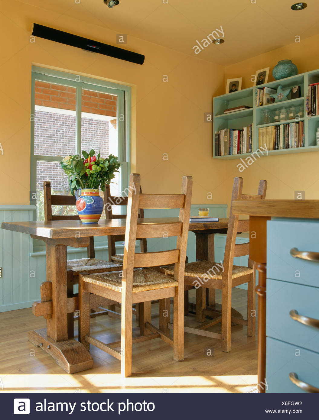 Wooden table chairs in yellow country kitchen with blue dado ...