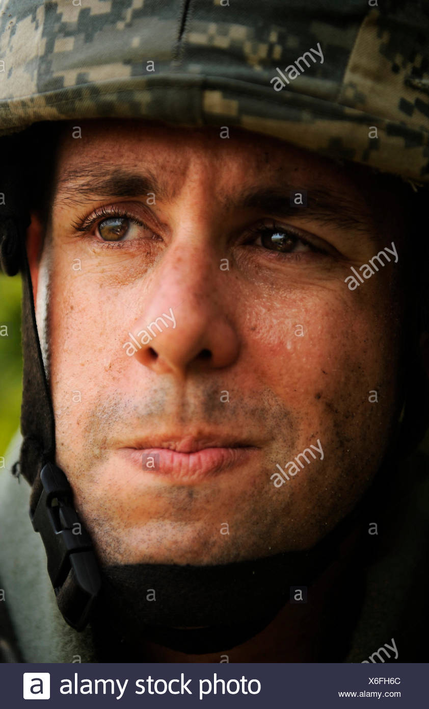 A soldier demonstrates the proper wear of body armor. The soldiers grimaces slightly as sweat pools on his eyelids. - Stock Image