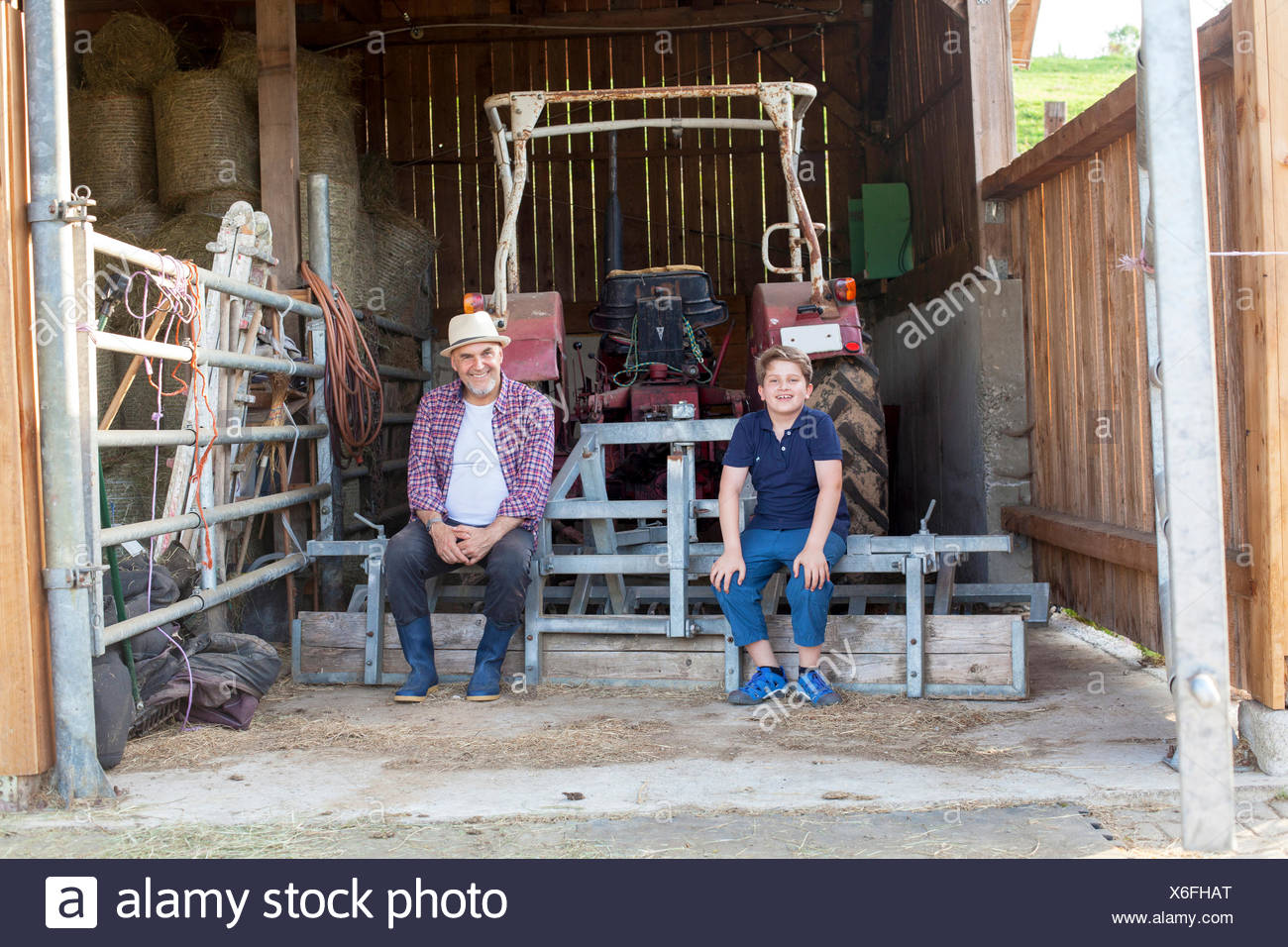 Grandfather and grandson taking a break in stable - Stock Image