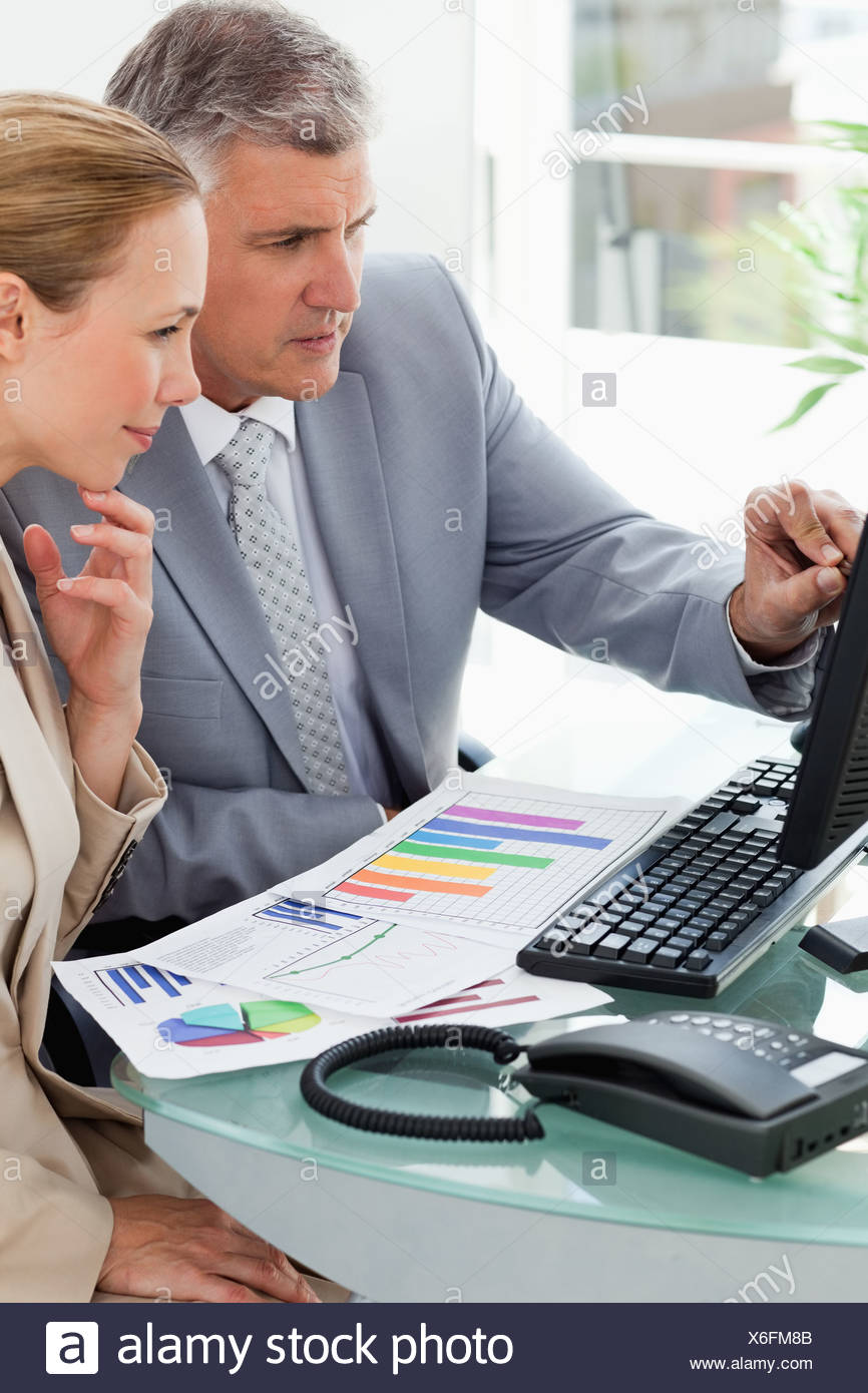 Business people working on statistical report - Stock Image