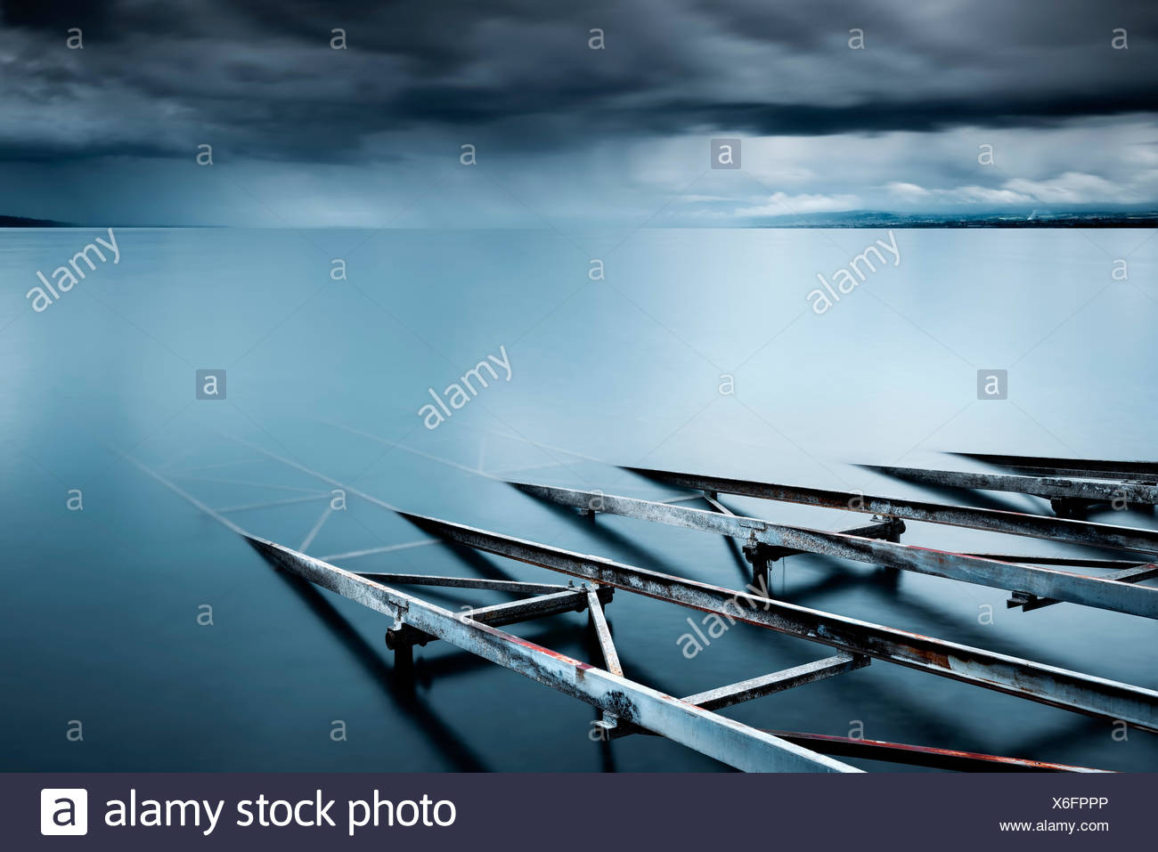 Switzerland, Vaud, Villette, Lake Leman, Slipway in still lake with storm clouds on horizon - Stock Image