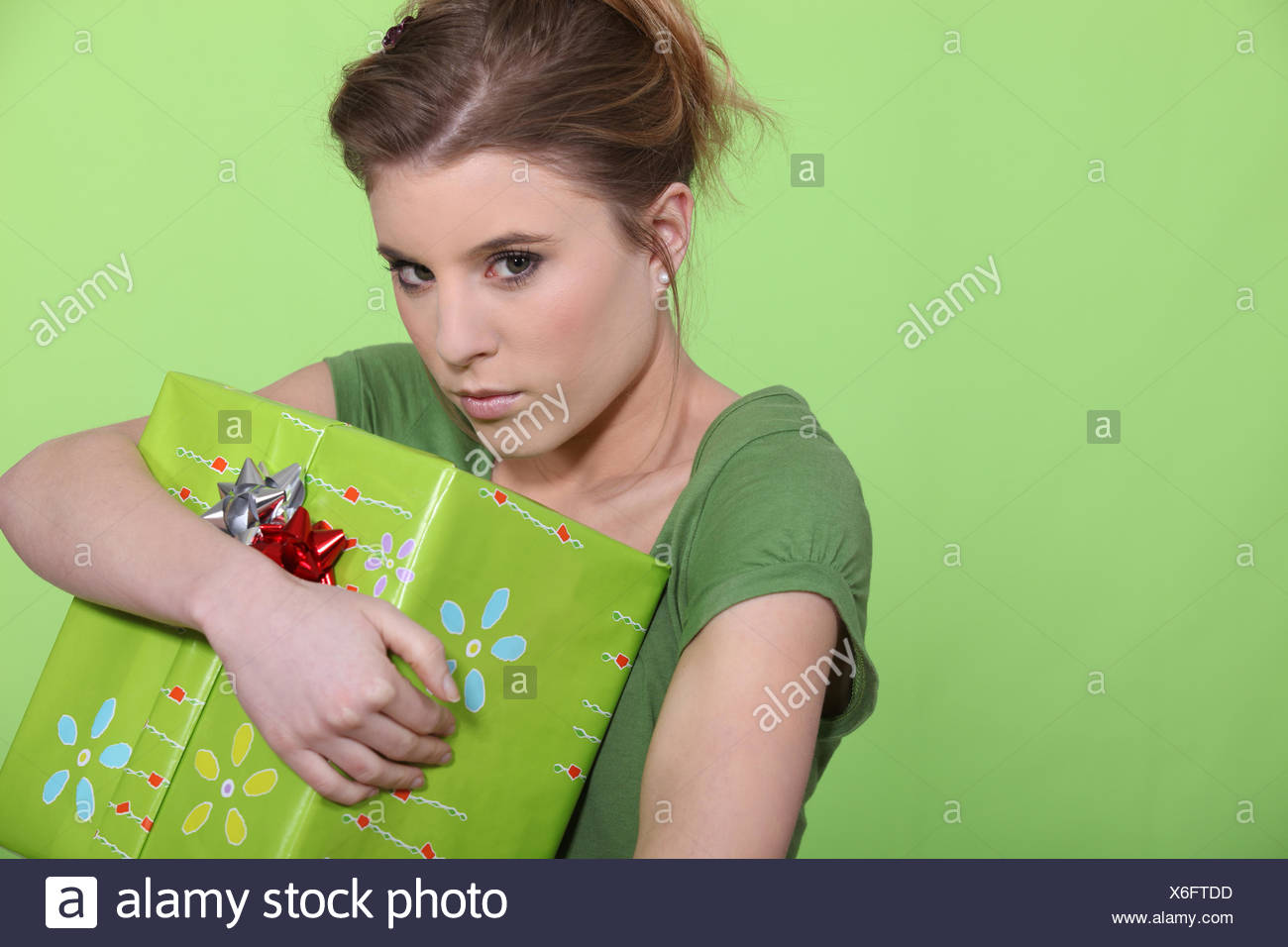 Greedy woman hugging her present all to herself - Stock Image