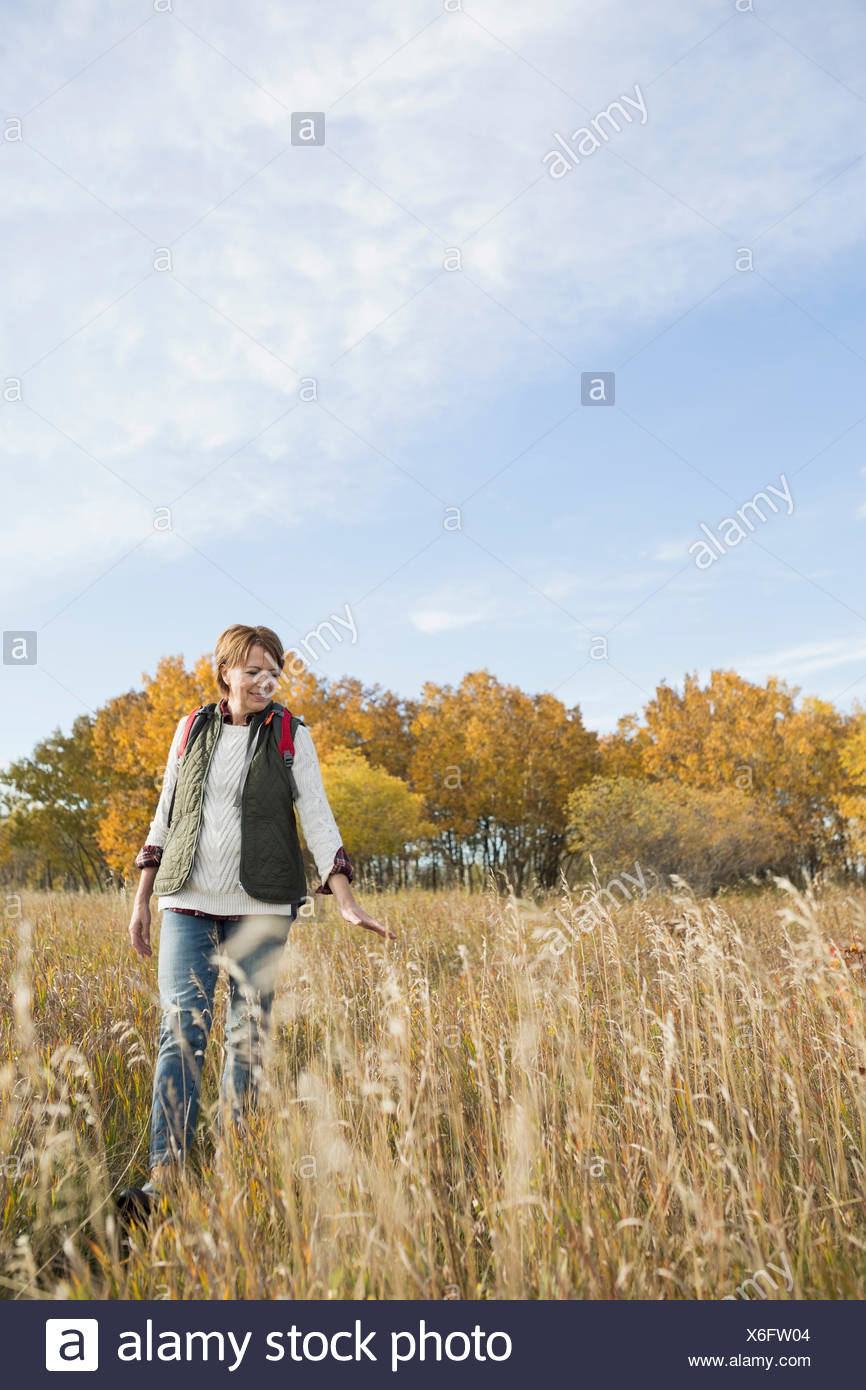 Woman walking in autumn field - Stock Image