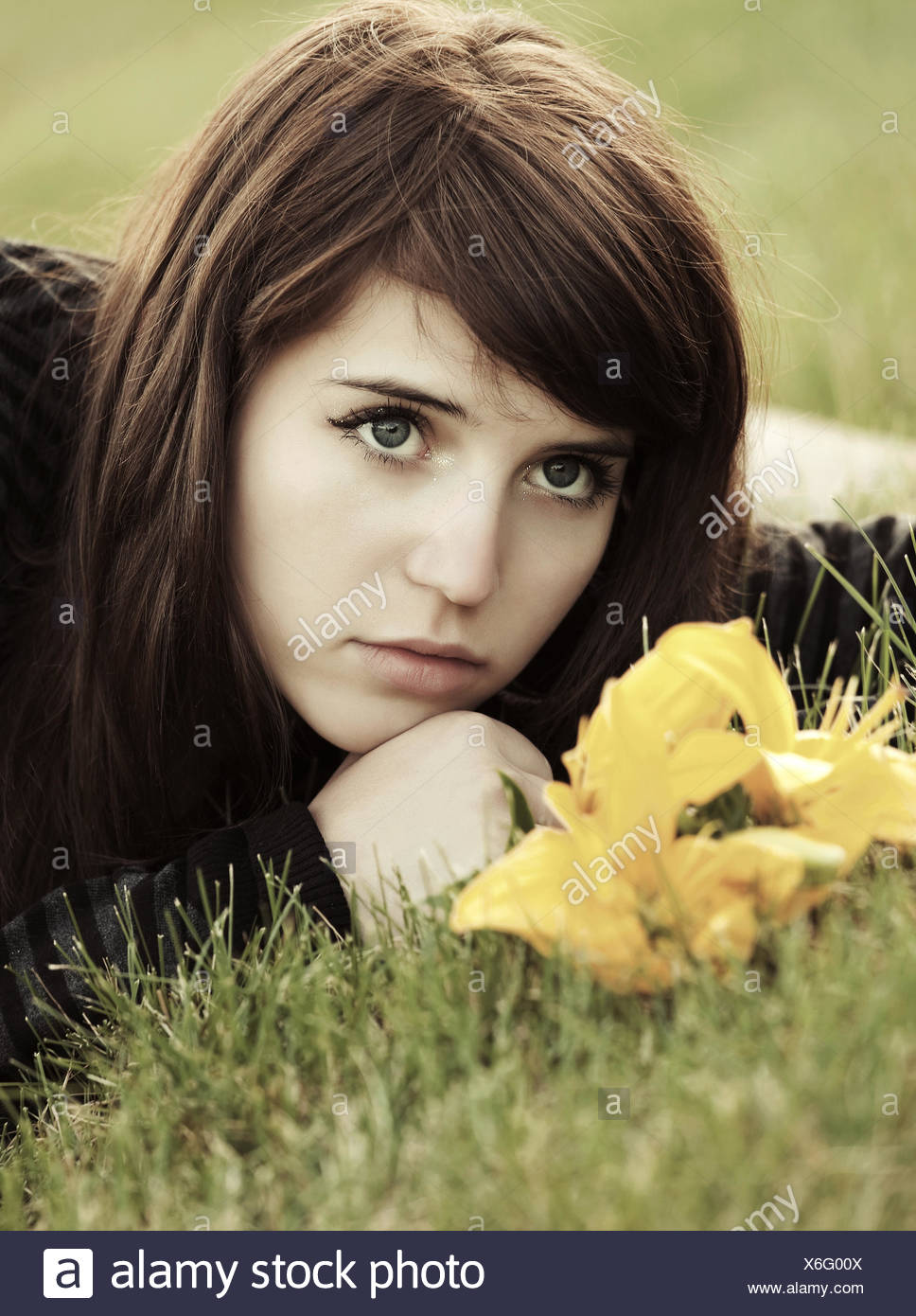 Sad young woman with a flowers lying on the grass - Stock Image