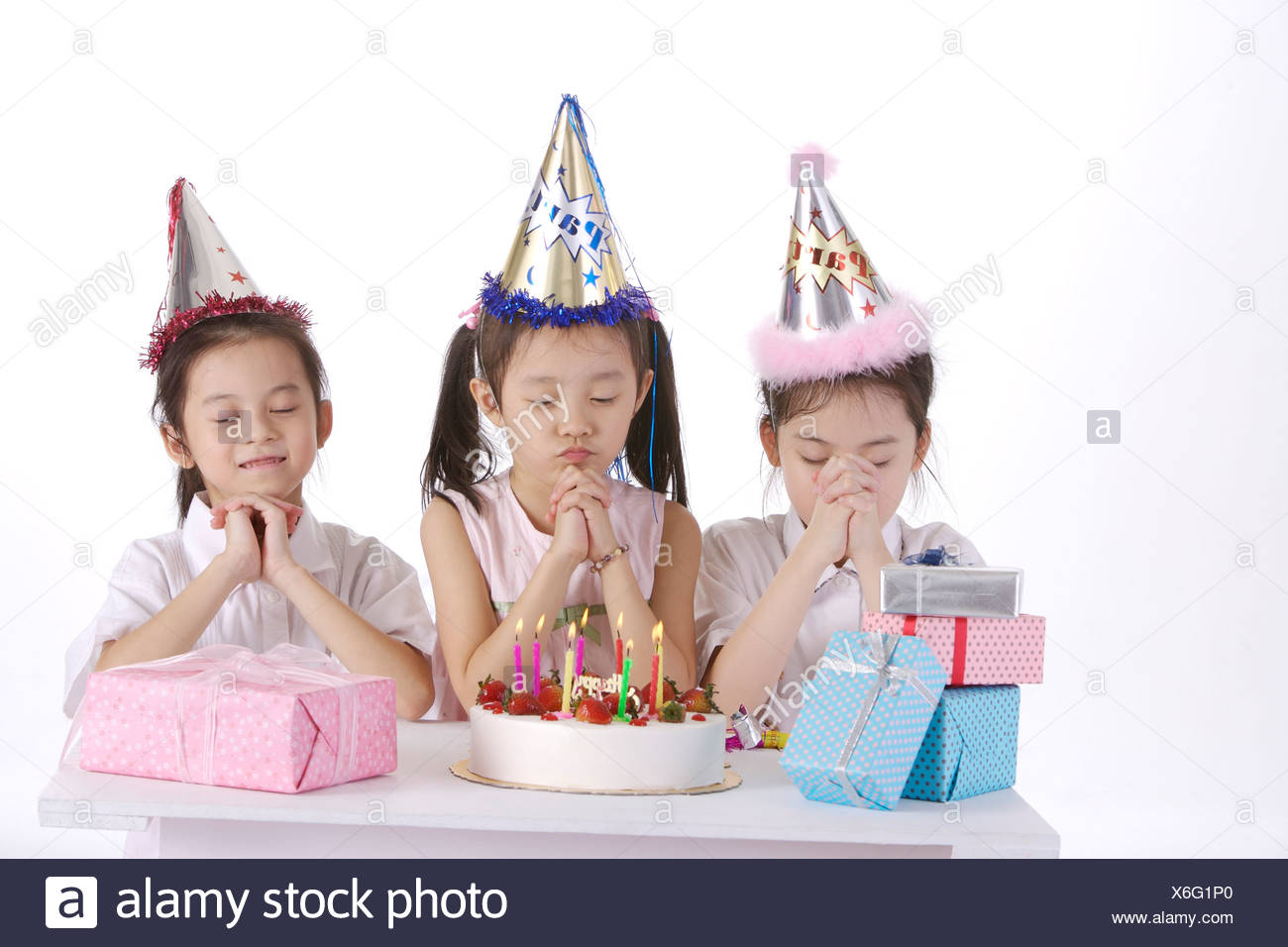 Marvelous Three Girls Making Wish Birthday Cake And Ts On Table Stock Personalised Birthday Cards Sponlily Jamesorg