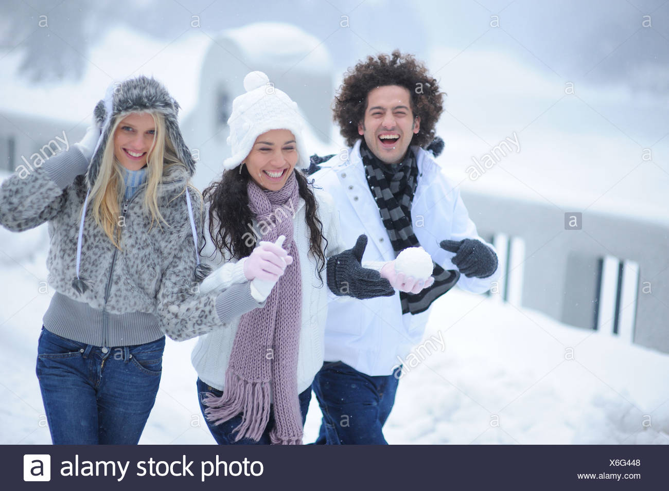 Young adult friends walking in the snow on winter day - Stock Image