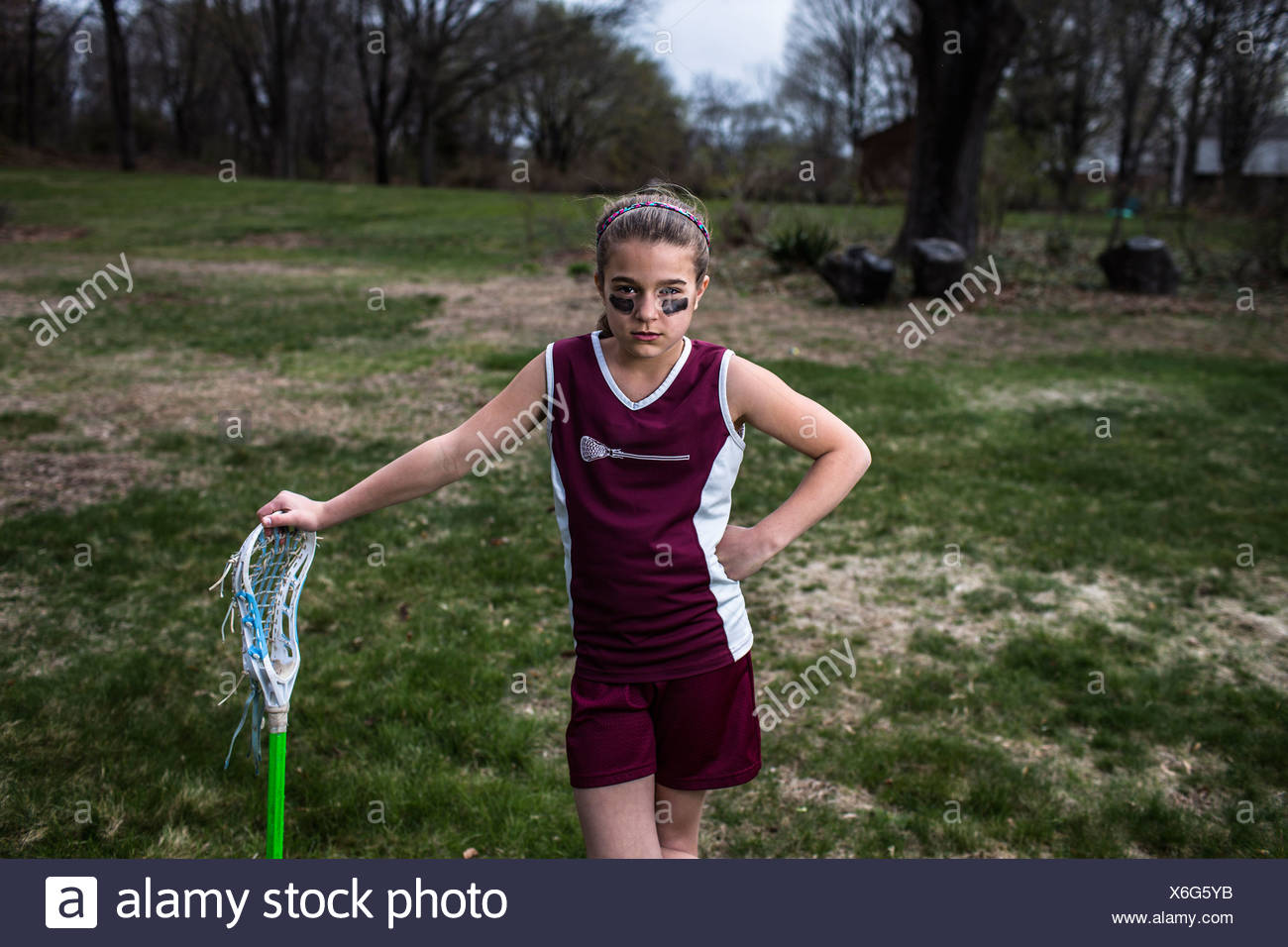 Girl wearing lacrosse uniform, leaning against lacrosse stick - Stock Image