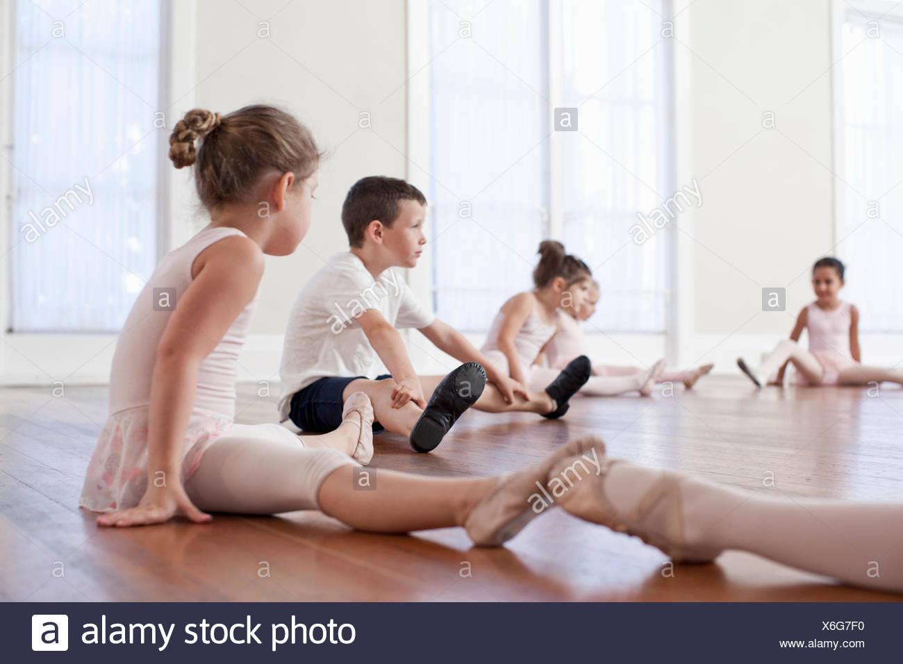 Children sitting on floor practicing ballet position in ballet school - Stock Image