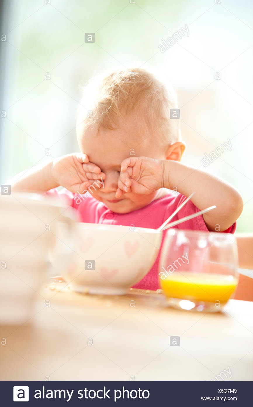 Tired baby at beakfast table - Stock Image