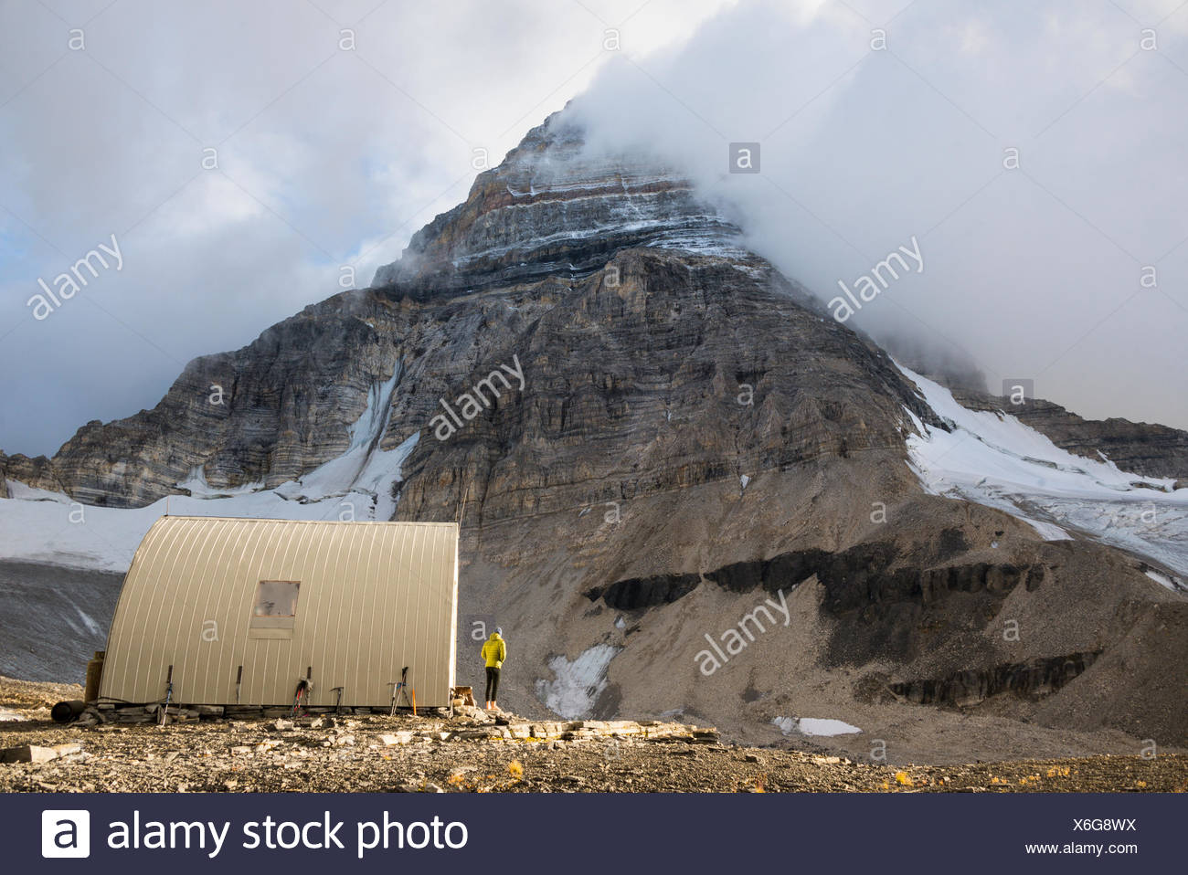 A climber scopes the summit while at the R.C. Hind hut below Mt. Assiniboine Stock Photo
