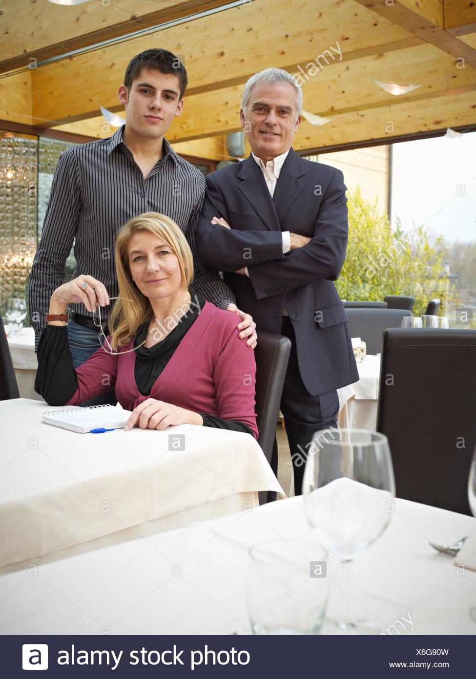 Mother Father and Son in a Restaurant. Handing down the business - Stock Image