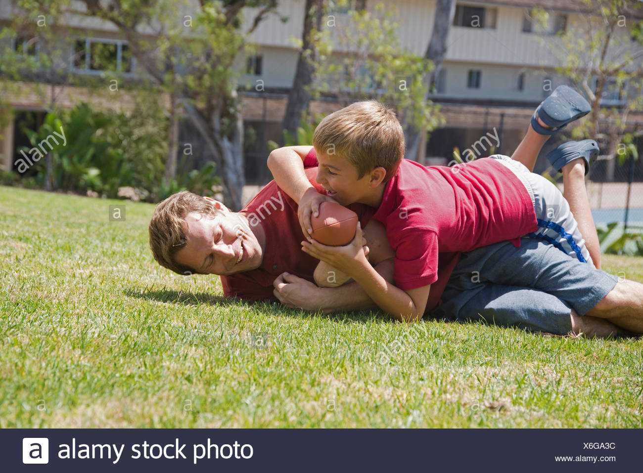 Boy tackling father playing american football in park - Stock Image