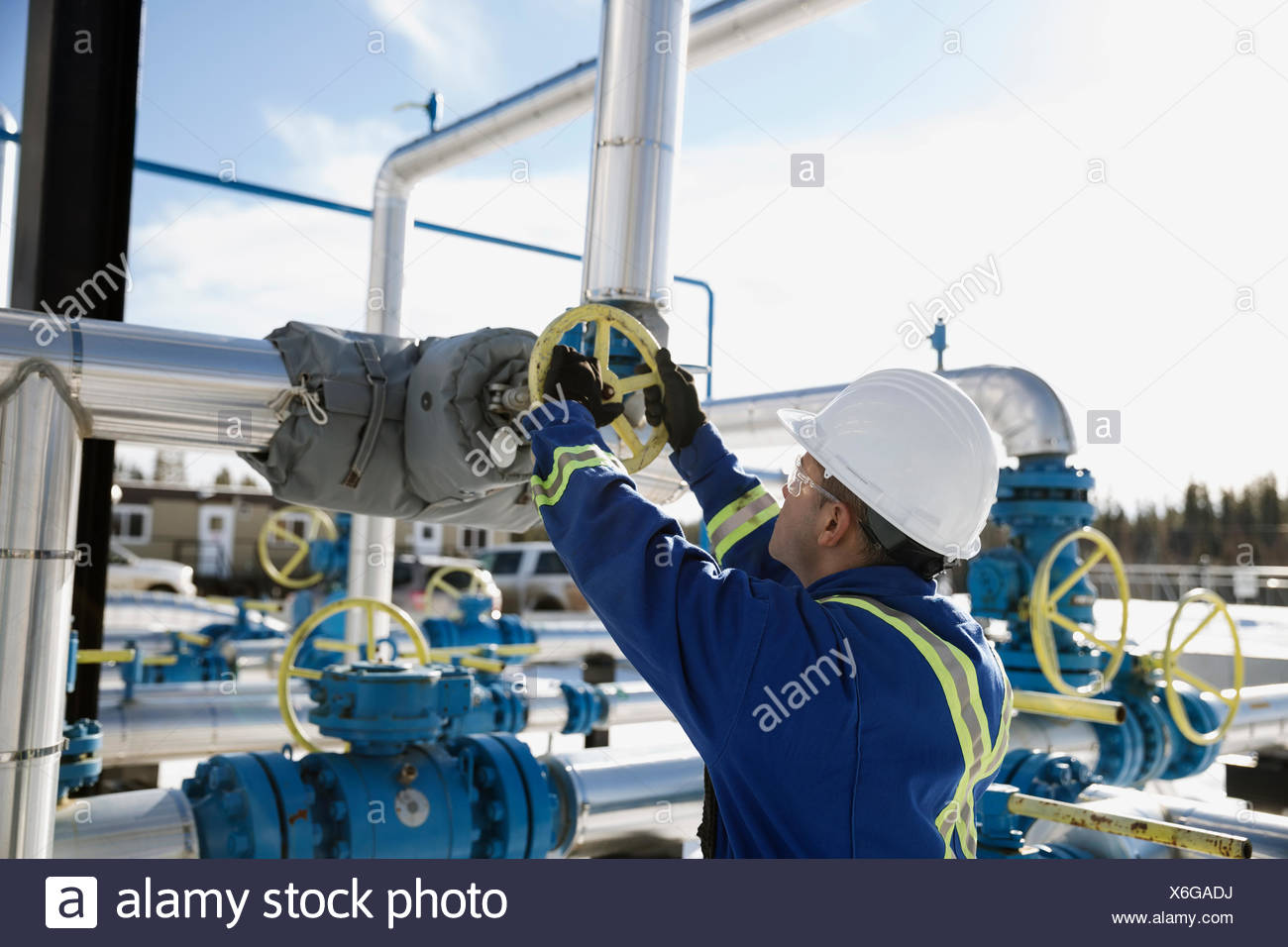 Male worker turning valve on gas plant pipeline - Stock Image