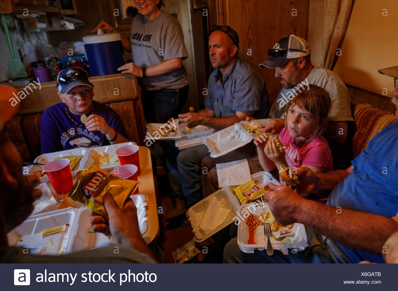 A family parks an RV in the field during the harvest so they can escape the elements and the bugs while they eat. Stock Photo