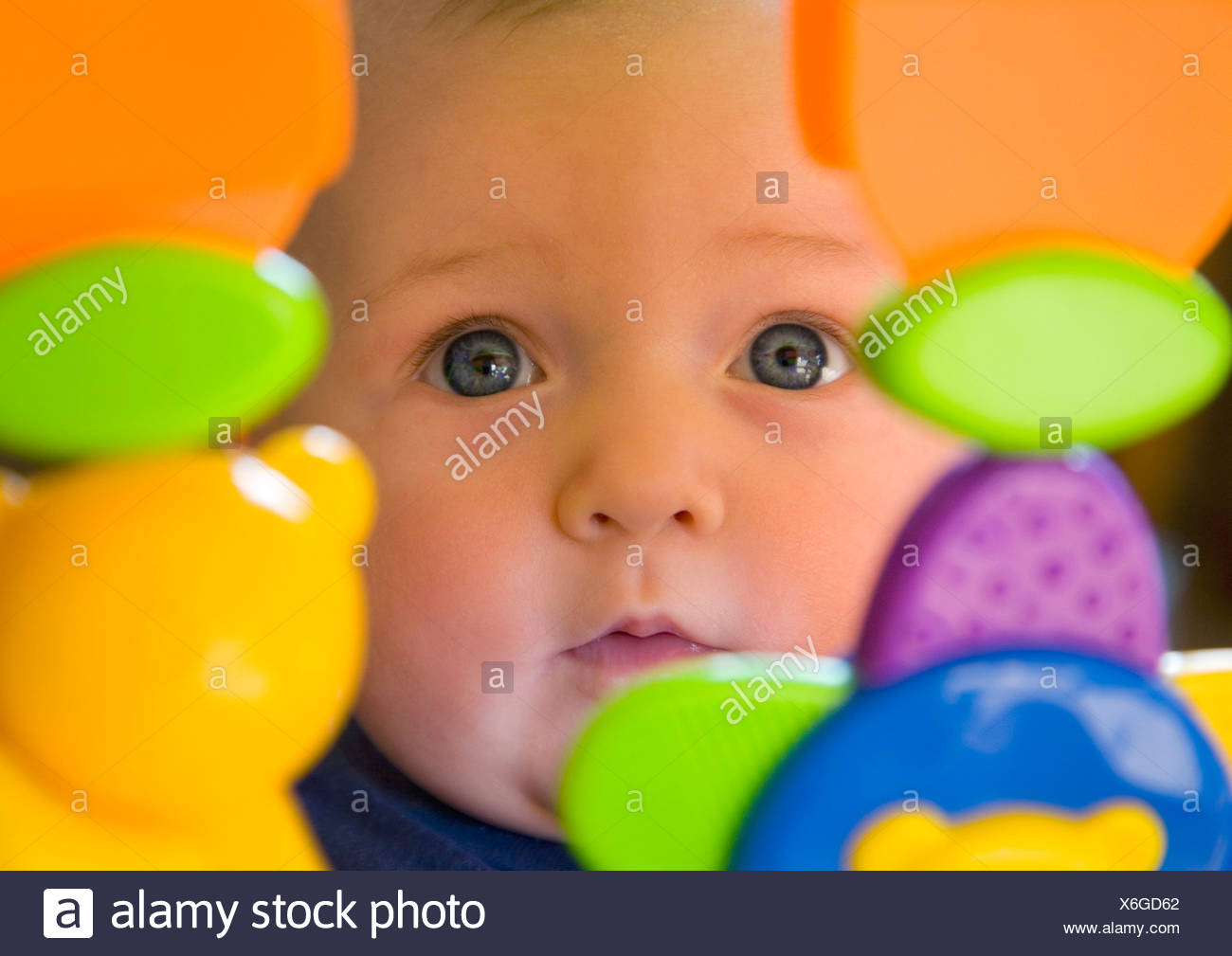 Baby girl 6 month old toddler with blue eyes looking through plastic toys - Stock Image