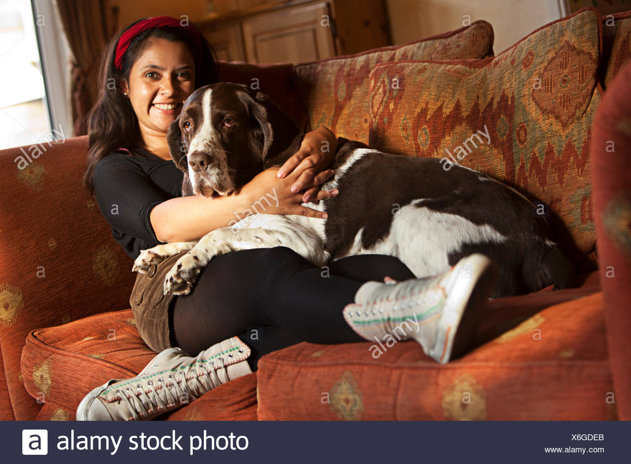 Woman sitting on couch with her dog - Stock Image