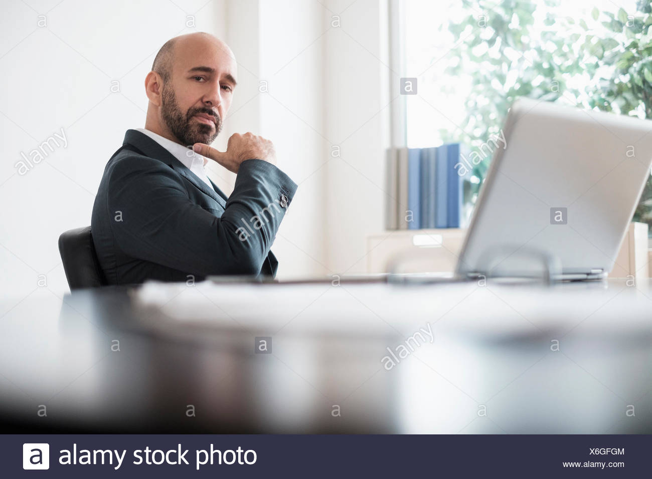 Serious businessman sitting at desk in office - Stock Image