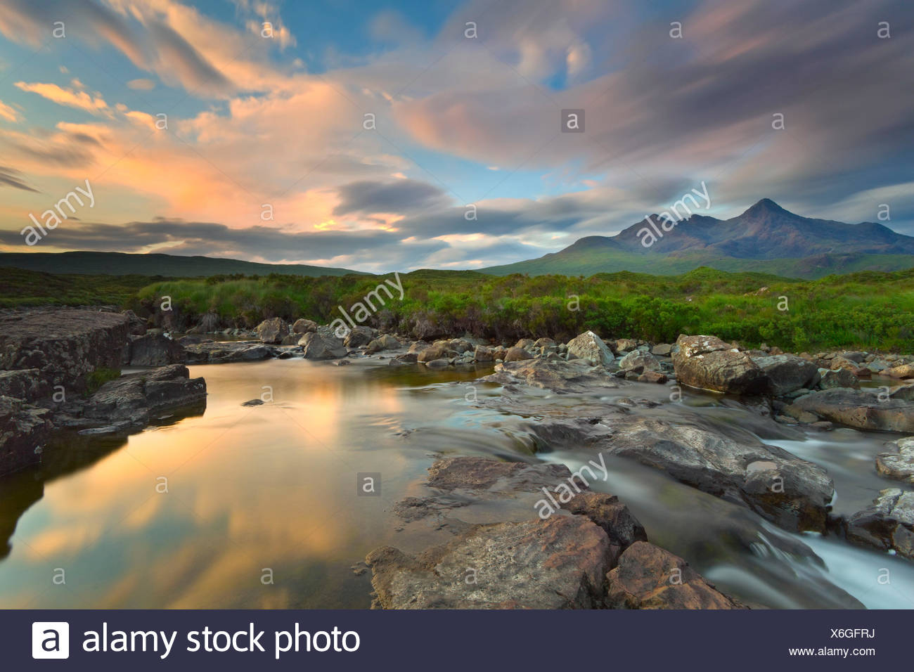 Isle of Skye, Scotland, Europe. The last sunset colors reflected in the water. In the background the peaks of the Black Cuillin. - Stock Image