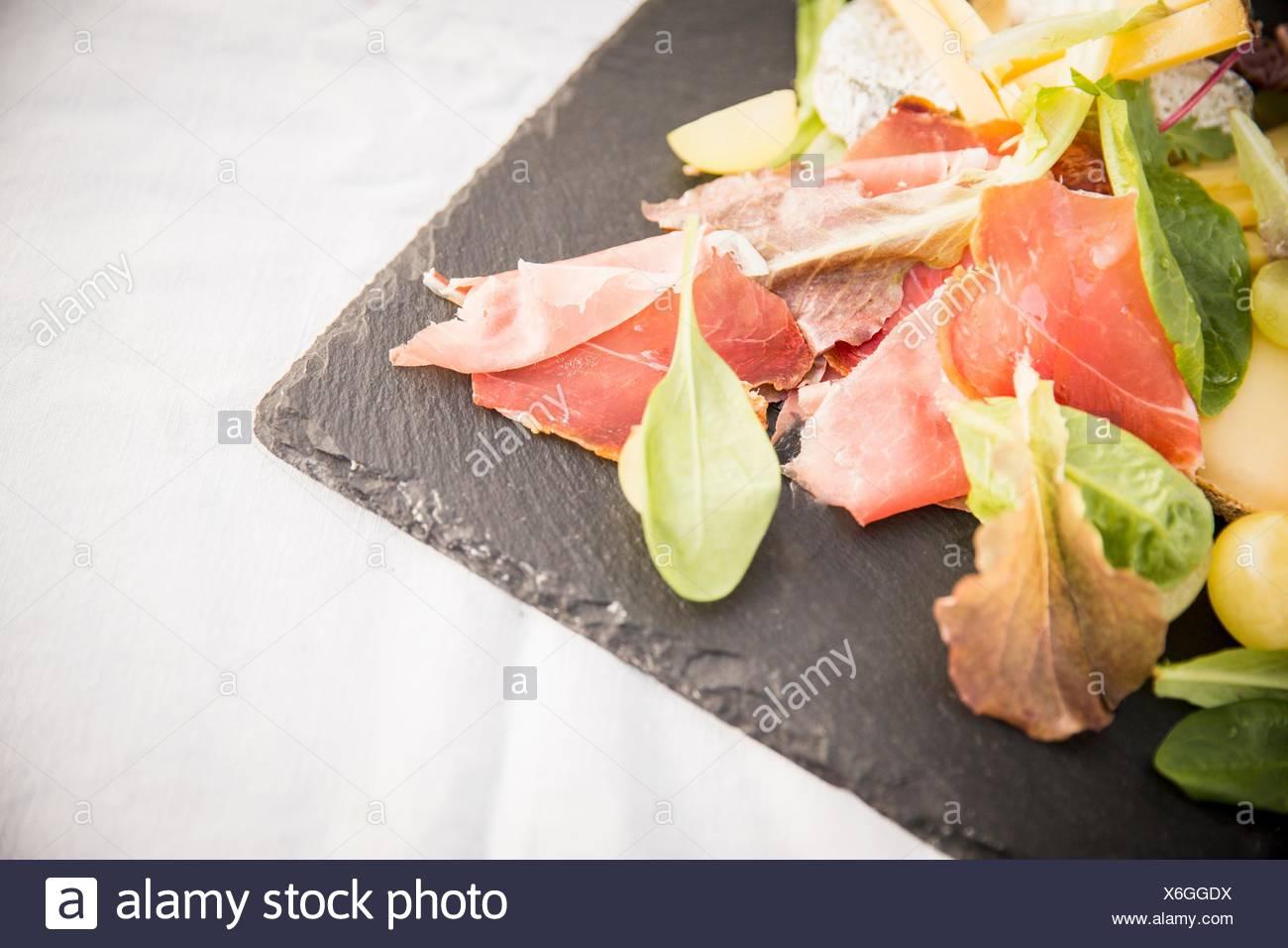 Ham and salad leaves on slate, close-up - Stock Image