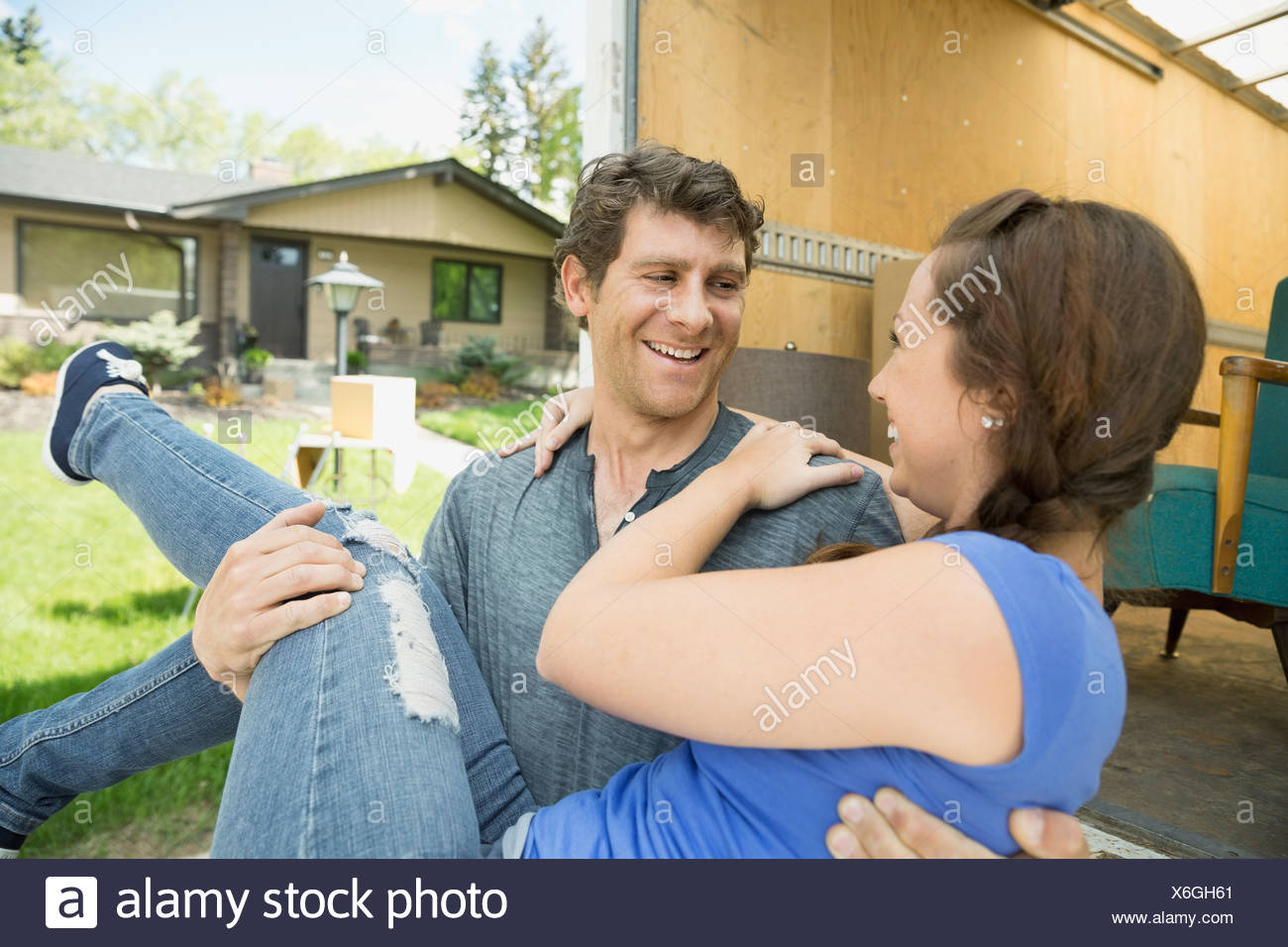 Man carrying woman outside moving van - Stock Image