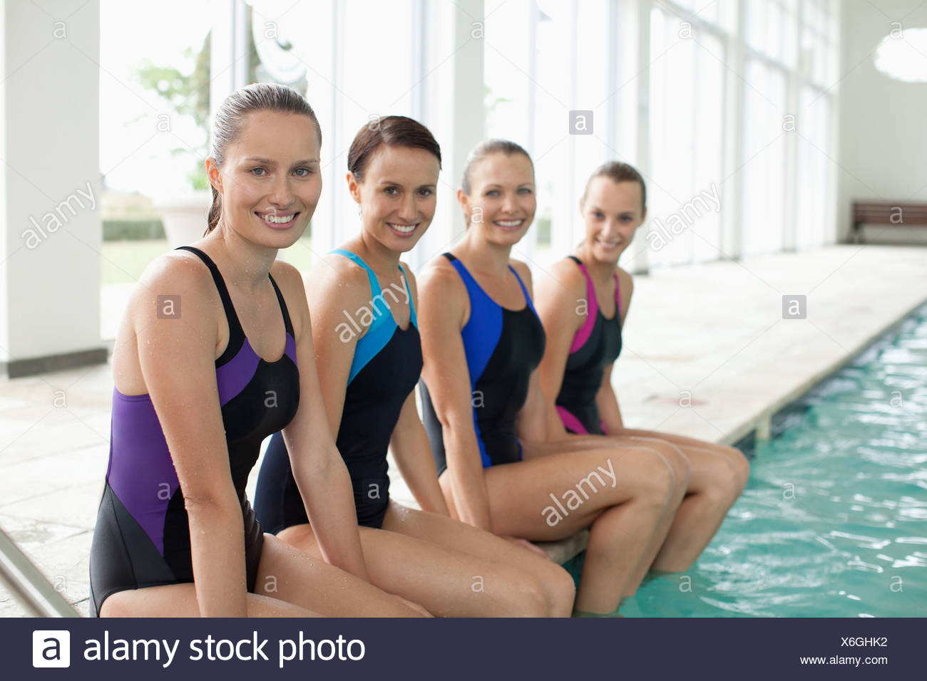Portrait of smiling swimmers with feet in swimming pool - Stock Image
