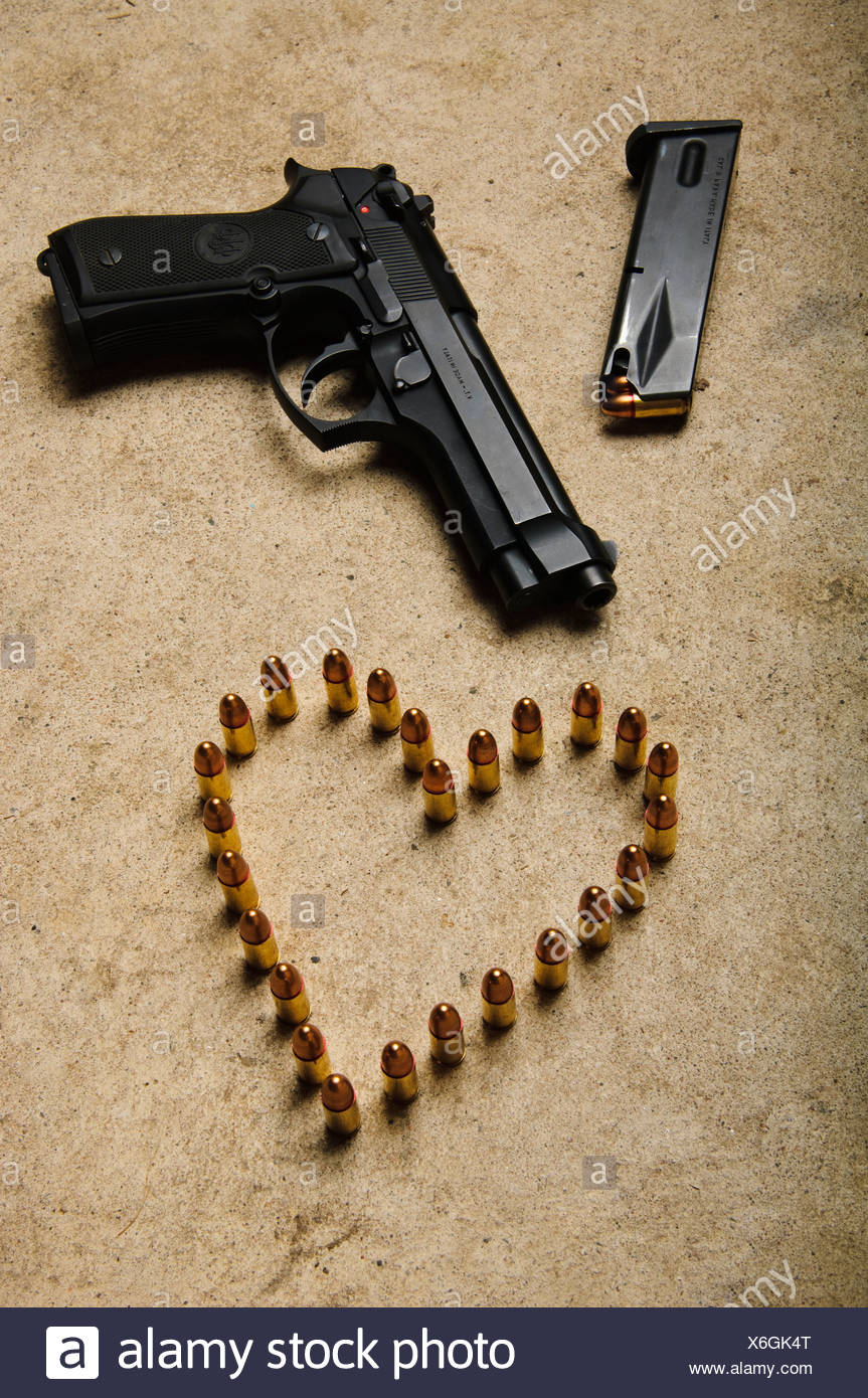 A gun and ammunition formed into a heart. - Stock Image