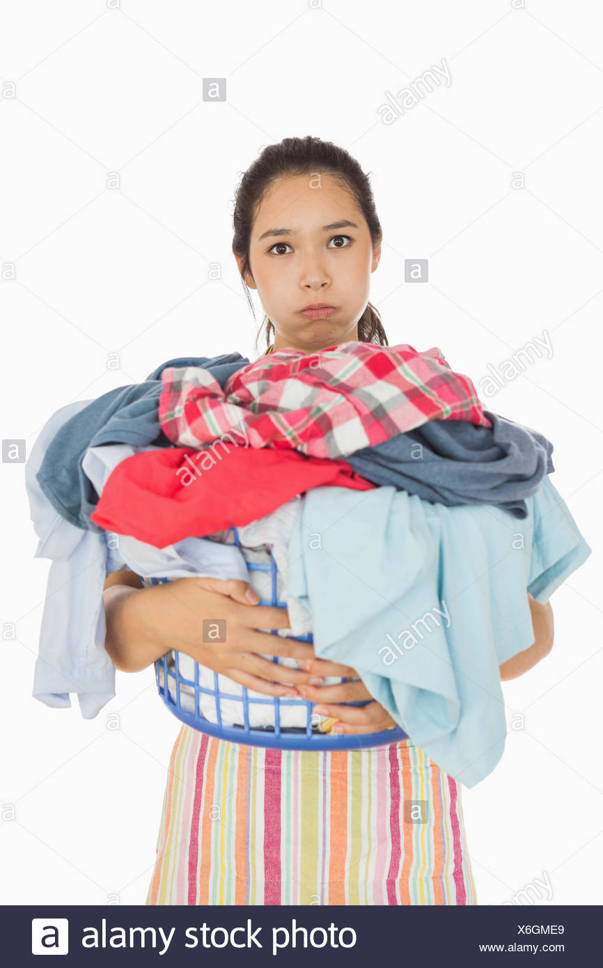 Tired woman holding full laundry basket - Stock Image