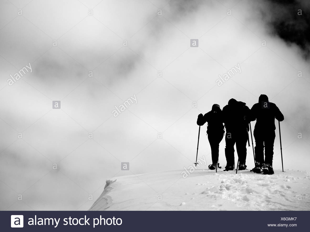 A group out snow shoeing on an overcast day. - Stock Image