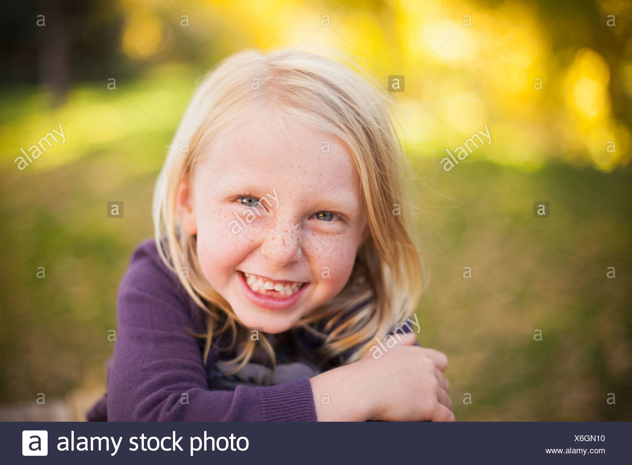 A girl sitting on the grass, smiling a big toothy smile. Close up. - Stock Image
