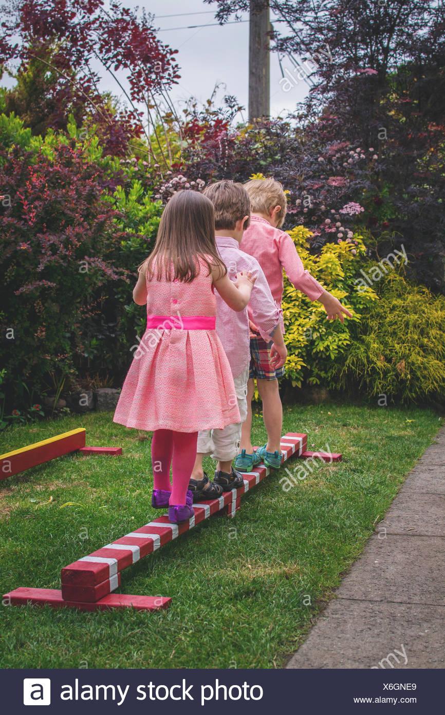 Three children walking across wooden pole - Stock Image