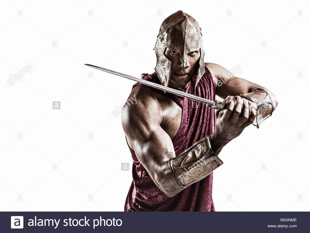Studio portrait of muscular young man dressed as gladiator with helmet and sword - Stock Image