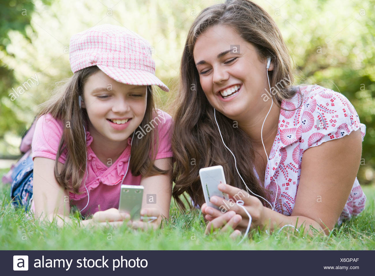 Young woman and a girl lying on grass in a park and listening to MP3 players - Stock Image
