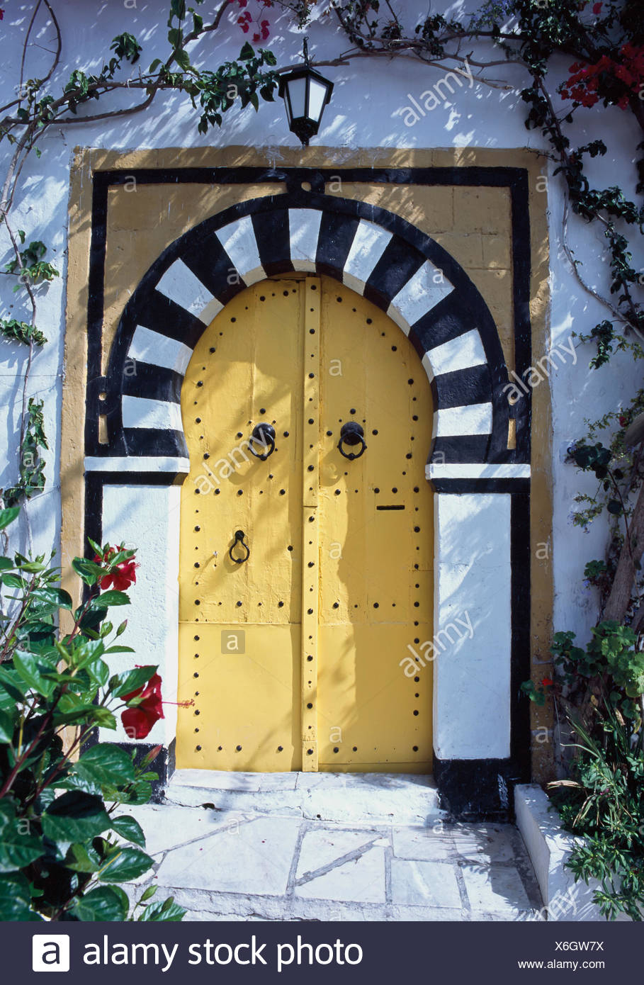 Black And White Arched Doorway With Yellow Doors. - Stock Image