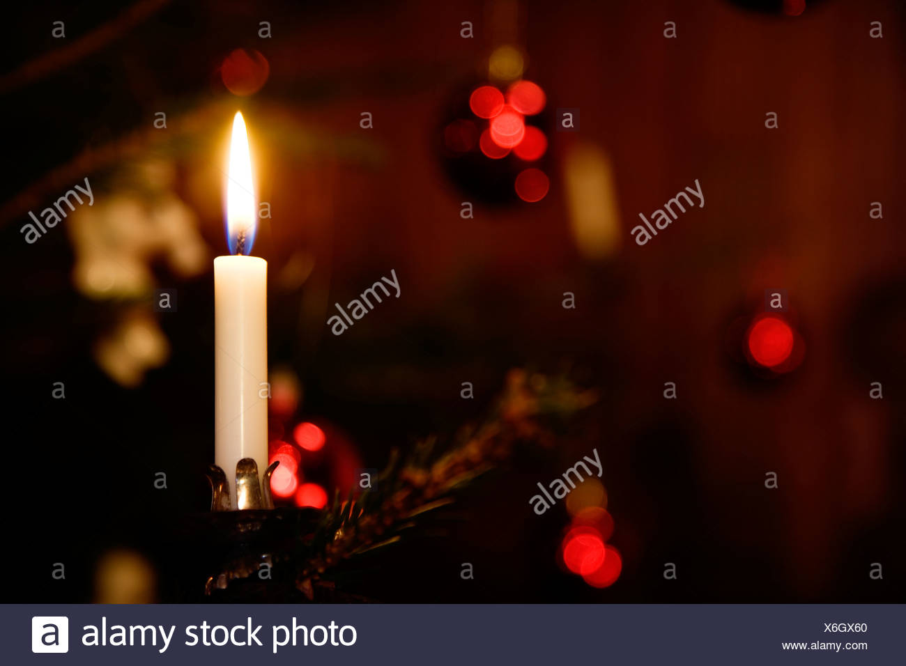 A candle in a Christmas tree close-up. - Stock Image