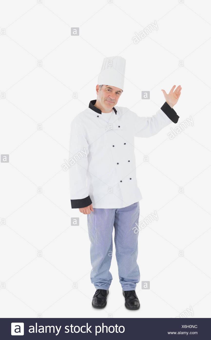 Mature chef displaying something on white - Stock Image