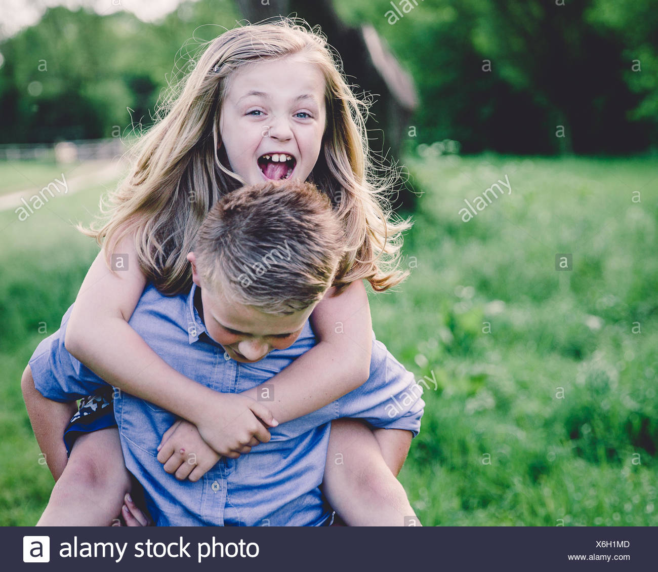 Siblings (8-9, 10-11) enjoying themselves in countryside - Stock Image