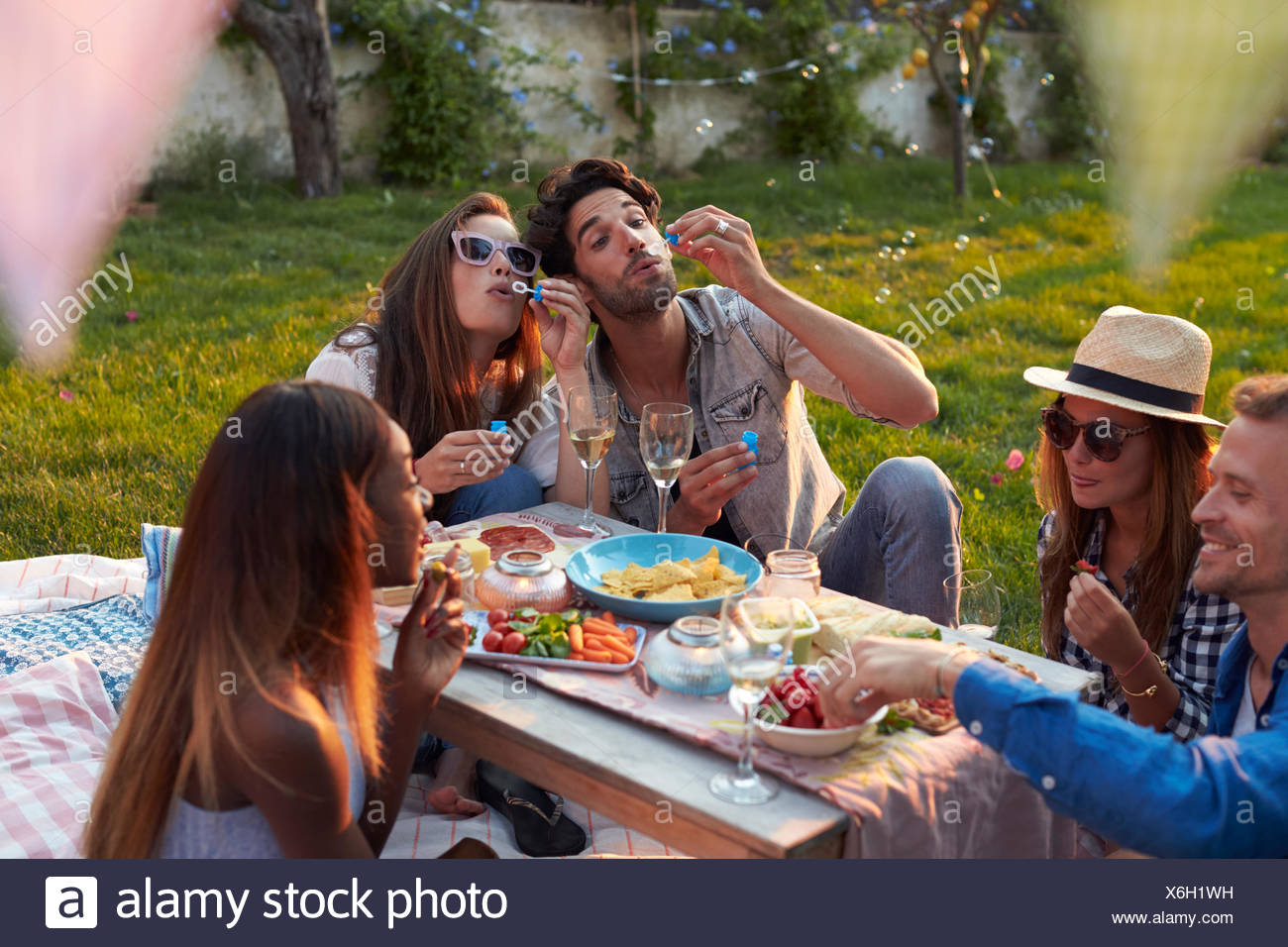 Friends Blowing Bubbles During Picnic In Garden Stock Photo